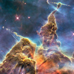 """Hubble captures a view of """"Mystic Mountain""""— pillars of gas and dust with jets emanating from the centers of disks around young stars in the Carina Nebula. Credit: NASA, ESA, and M. Livio and the Hubble 20th Anniversary Team (STScI)."""
